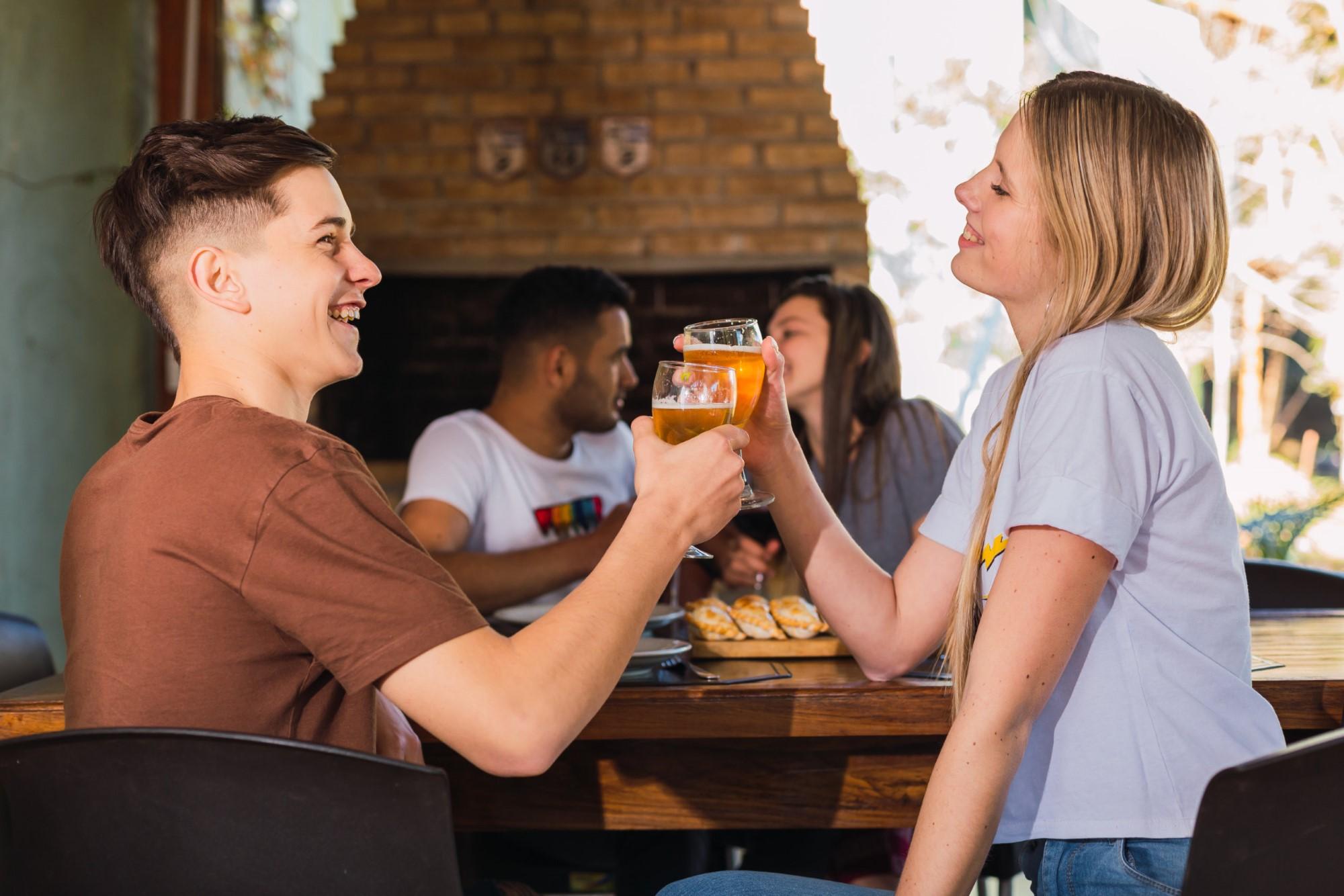 Brindis entre hombre y mujer restaurante con empanadas
